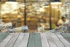 Pulvérisez la neige par le fond de vitrail avec la table en bois photos stock