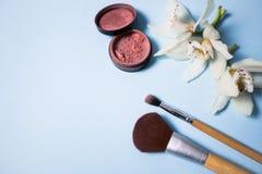 Pulver, Bürste und Blume auf einem blauen Hintergrund Stockfotografie