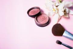 Pulver, Bürste und Blume auf rosa Hintergrund Lizenzfreies Stockbild