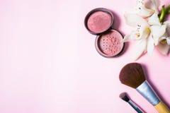 Pulver, Bürste und Blume auf rosa Hintergrund Lizenzfreies Stockfoto