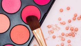 Pulver in den Bällen mit einem leuchtenden Effekt auf den Hintergrund des Satzes für erröten Make-upkosmetikbürste lizenzfreie stockfotografie