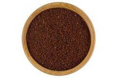 Pulver des gemahlenen Kaffees in einer hölzernen Schüssel lokalisiert auf weißem backgrou Stockfotografie