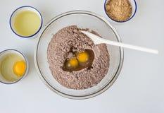 Pulver för kakablandning och rå ägg i en glass bunke Arkivbilder