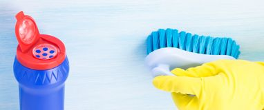 Pulver für Reinigungsoberflächen in einer blauen Dose und in einer Gummi-behandschuhten Hand, die eine Bürste auf einem hellen Hi lizenzfreies stockbild