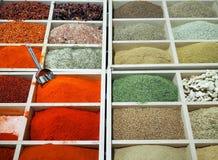 Pulver kryddar det färgrika sortimentet i träaskar på en marknadshyllaställning arkivfoto