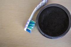 Pulver och tandborste för aktiverat kol arkivbild