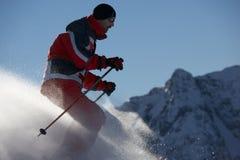 Pulverisieren Sie Skifahrer infront der Berge lizenzfreies stockbild