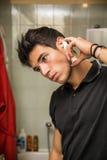 Pulverizador de pulverização da orelha do homem novo nas orelhas Fotos de Stock Royalty Free