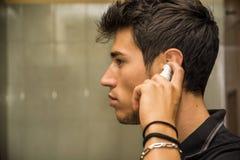 Pulverizador de pulverização da orelha do homem novo nas orelhas Fotografia de Stock Royalty Free