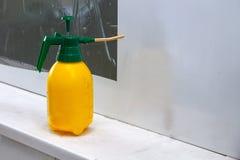 Pulverizador industrial amarelo com uma tampa verde para a água de pulverização na oficina para colar o filme em um fundo branco  foto de stock royalty free