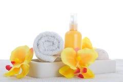 Pulverizador, toalha e orquídea amarela Fotos de Stock