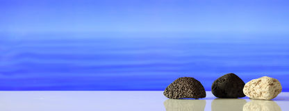 Pumice rocks on blue sea background Royalty Free Stock Photos