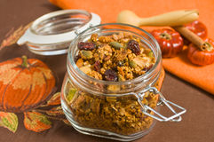 Pumkin Granola. In a clear jar on brown table cloth with small pumpkins Royalty Free Stock Photo