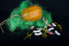 Pumkin and round, teeth, worm shaped sweets. Pumkin in green grass and round, teeth, worm shaped multycolored sweets on black background Stock Photos