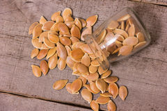 Pumkin seeds pile. On a wooden background royalty free stock images