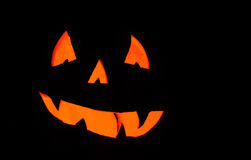Pumkin smile. Smiling face of a pumpkin orange light illuminated from the inside with a pitch black background Stock Photo
