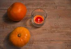 Pumkins arancio con la candela variopinta nel vetro sui bordi di legno fotografia stock libera da diritti