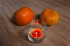 Pumkins oranges avec la bougie colorée dans le verre sur les conseils en bois image libre de droits