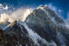 Himalayan summit Pumori against a blue sky with clouds. Everest Royalty Free Stock Photo