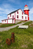 The Pump. Ferryland Lighthouse in Newfoundland showing Rusted Pump in Foreground and Lighthouse in Background on Sunny Day Stock Photos