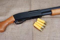 Pump shotgun. Pump action shotgun on canvas background Stock Photo