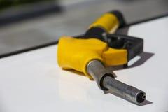 Pump f?r bensinstation f?r dysa f?r br?nsle f?r bensinpistolpump Man som tankar bensin med br?nsle i en bil som rymmer en dysa In arkivfoto