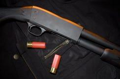 Pump gun. Orange gel from above on a pump action shotgun and ammunition Stock Images