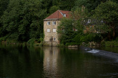 Pump house beside a quite river bank Royalty Free Stock Images