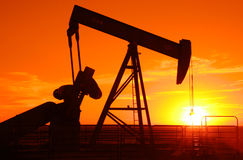 Pump jack 2. Oil field pump jack silhouette with setting sun Stock Photos
