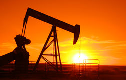 Pump Jack 7. Oil field pump jack with a setting sun in background Royalty Free Stock Photos