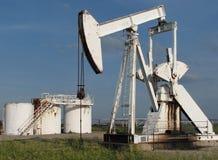 Pump jack. Oil pump jack and tanks stock images