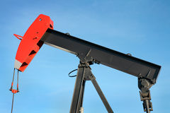 Pump jack close. Close up view of a black and red oil pump jack against blue sky royalty free stock images