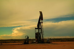 Pump jack and clouds Stock Photography
