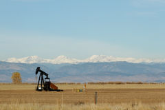 Pump Jack in A Colorado Field with Mountains in the Background. A oil rig sits in a field with the snow capped mountains in the background royalty free stock photo