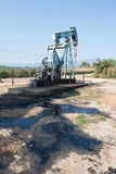 Pump jack with crude oil contamination Royalty Free Stock Photo