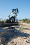 Pump jack with crude oil contamination Royalty Free Stock Images