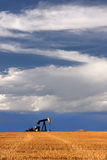 Pump Jack. Drilling on a field against a sky with white clouds Royalty Free Stock Images