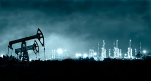 Pump jack and grangemouth refinery at night. Royalty Free Stock Photos