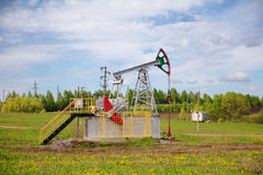 Pump jack with a green field in background Royalty Free Stock Image