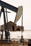 Pump jack near abandoned homestead Stock Photography