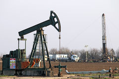 Pump jack and oil drilling rig stock image
