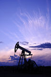 Pump jack. Oil and gas industry. Oil and gas industry. Silhouette oil pump on a purple sunset sky background. Siberia, Russia Stock Image