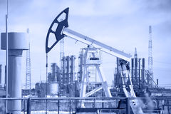 Pump jack and oil refinery. Royalty Free Stock Image