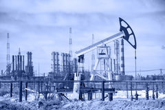Pump jack and oil refinery. Toned. Royalty Free Stock Photo