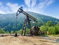 Oil well with pump-jack in the Carpathian Mountains. Pump-jack pumping petroleum on oil well located in the Carpathian Mountains royalty free stock images