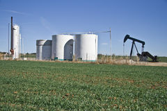 Pump Jack and Tank Farm-6884. Pump Jack and it's Tank Farm in the middle of an Oklahoma wheat field Royalty Free Stock Photos