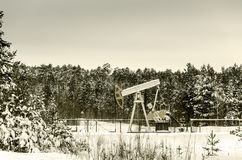 Pump jack and wellhead in the oilfield Royalty Free Stock Image