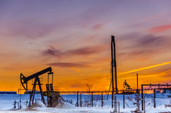 Pump jack, wellhead, pipeline and oil rig during sunset Royalty Free Stock Photos