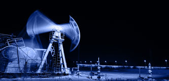 Pump jack and wellhead. Toned blue. Stock Images