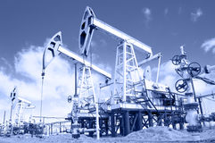 Pump jack and wellhead. Toned. Royalty Free Stock Photo